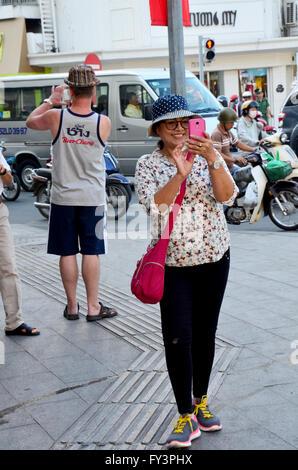 Traveller use smartphone take photo traffic of Saigon city on January 22, 2016 in Ho Chi Minh, Vietnam - Stock Photo