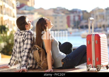 Side view of a couple of 2 tourists with a suitcase sitting relaxing and enjoying vacations in a colorful promenade. - Stock Photo