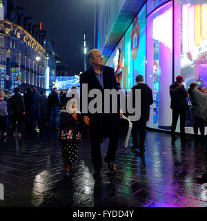 Man holding young girl by the hand whilst walking on wet pavement at night in London - Stock Photo