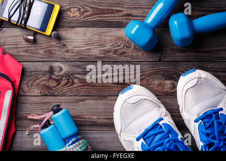 Sports equipment - sneakers, skipping rope, dumbbells, smartphone and headphones. Sport background on wooden floor, - Stock Photo