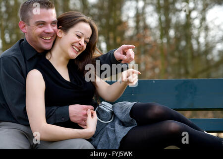 Young couple on a bench having fun - Stock Photo