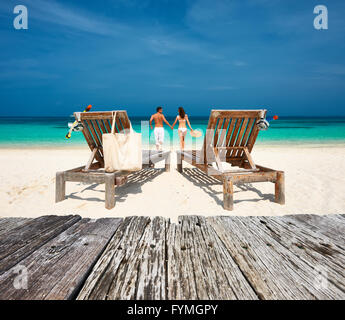 Couple in white relax on a beach at Maldives - Stock Photo