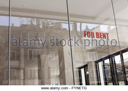 FOR RENT - sign on the window of an empty shop, store or street venue with reflections of a house in the glass - Stock Photo