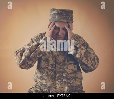 A stressed army man is holding his hands to his head on an  isolated background for a war effect or pain concept - Stock Photo