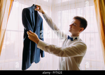 Young man in white shirt and bow-tie holds  business jacket coat - Stock Photo