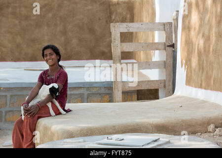 Unidentified young Indian girl  sits in front of her house and hugs a baby lamb in rural areas of Jaisalmer, India - Stock Photo