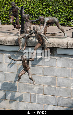 First Generation. A Sculpture of Five Boys Leaping into the Singapore River near Cavenagh Bridge in Singapore - Stock Photo