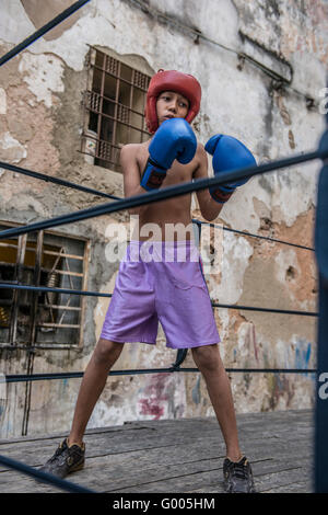Low angle view of a young Cuban boy wearing blue gloves and red headgear, sparring at Project Cuba Boxeo. Old Havana, - Stock Photo