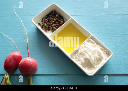 Radishes on two blue wooden background with salt, oil and pepper - Stock Photo