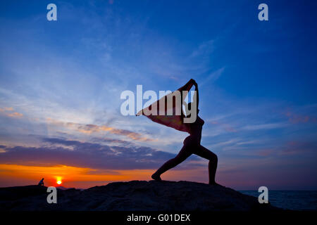 A silhouette of a women practicing yoga at sunset on beach - Stockfoto