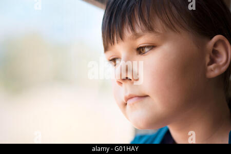 Girl is looking through window while sitting in train, closeup shoot - Stock Photo