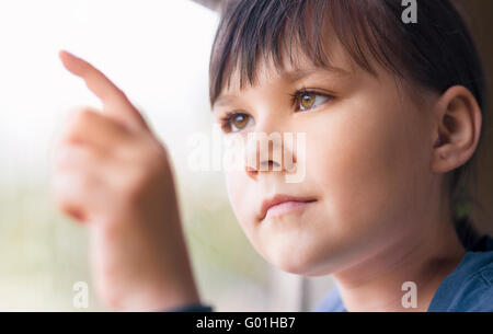 Girl is drawing something on window while sitting in train, closeup shoot - Stock Photo