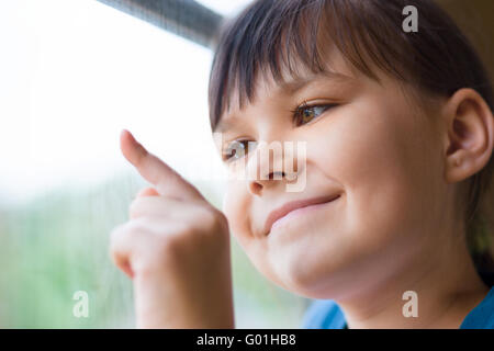 Happy girl is drawing something on window while sitting in train, closeup shoot - Stock Photo