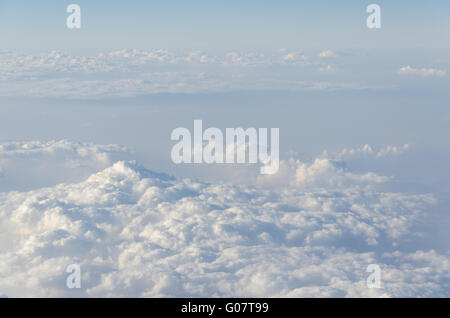 Clouds seen through plane window during flight. - Stock Photo