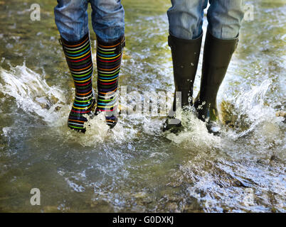 Happy couple wearing colorful rain boots - Stock Photo