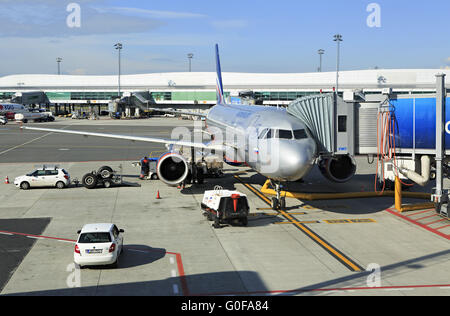 Commercial aircraft being serviced on the tarmac of an international airport. - Stock Photo