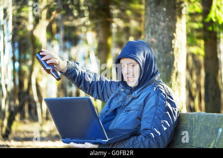 Man with beer bottle and PC in the park on a bench - Stockfoto