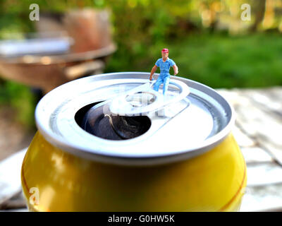 Miniature workman sitting on top of soda can with blurred background. Business concept - Stock Photo