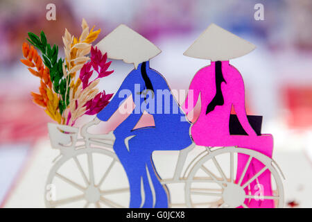 Vietnamese motif of women riding a bike and carrying flowers to the market - Stock Photo