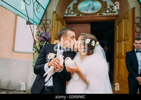 Happy newlyweds bride and groom with doves in hands on church doors background - Stockfoto