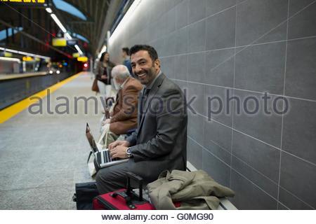 Portrait smiling businessman laptop bench subway station platform - Stock Photo