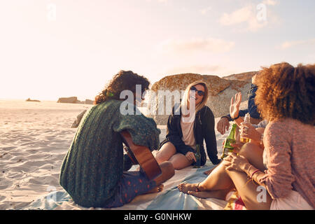 Portrait of young man playing guitar for friends. Group of friends having fun at the beach party. Young men and - Stock Photo