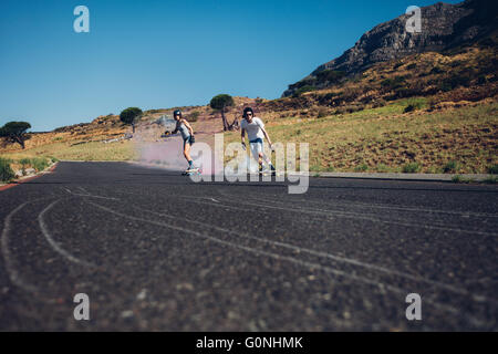 Young man and woman skateboarding with smoke bomb on the road. Young couple practicing skating on a open road. - Stock Photo
