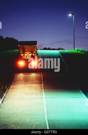 Truck traveling on road at night - Stockfoto