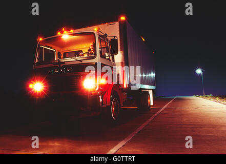 Truck traveling on road at night - Stock Photo