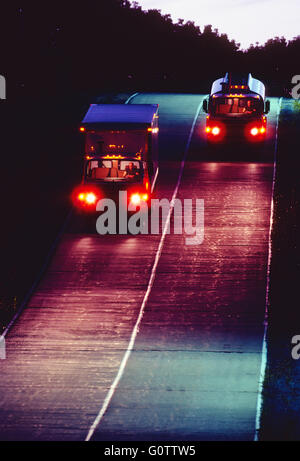 Trucks traveling on road at night - Stock Photo