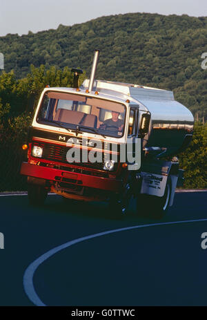 Fuel oil tanker truck traveling at dusk on rural road - Stock Photo