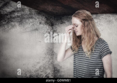 Composite image of blonde woman with headache pinching her nose - Stockfoto