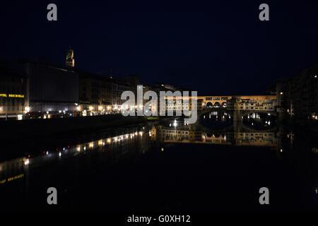 night view down the Arno to to the Ponte Vecchio bridge. - Stock Photo