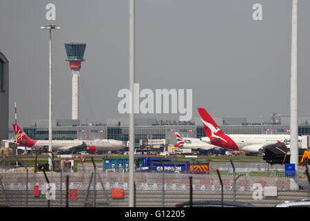 Busy London Heathrow Airport with gates and control tower - Stock Photo