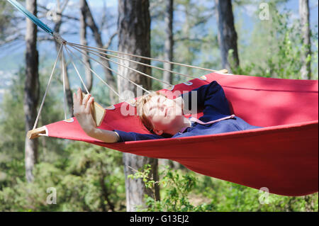 Young smiling girl enjoy in red hammock in forest. Relaxing on hammock with a smartphone. - Stock Photo