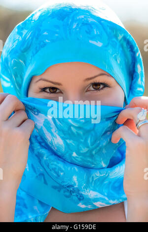 Portrait of a Muslim woman in a blue scarf close-up - Stock Photo
