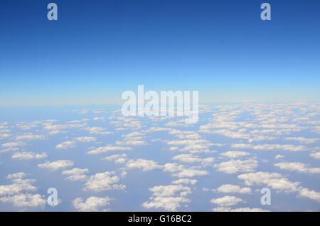 Clouds seen through airplane window during flight. - Stock Photo