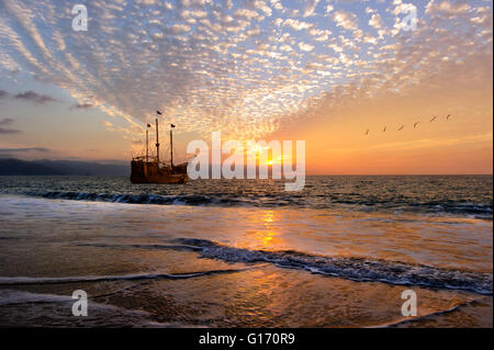 Ship sunset is an old wooden pirate ship with full flags as the sun sets on the ocean horizon in a colorful sunset - Stock Photo