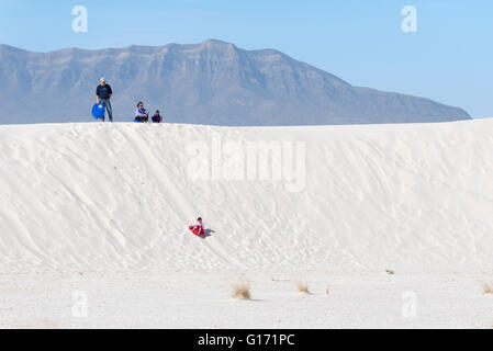 Family playing on dune in White Sands National Monument, New Mexico. - Stock Photo