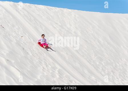 Girl sliding down dune in White Sands National Monument, New Mexico. - Stock Photo