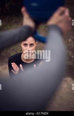 High angle view of woman looking up at friend holding kettle bell - Stock Photo