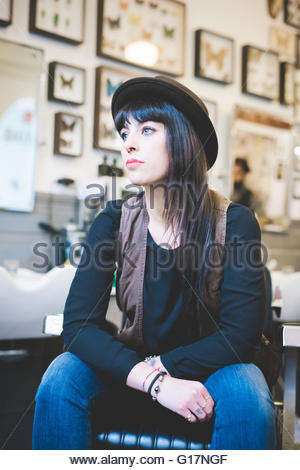 Female barber waiting for customer in shop - Stock Photo
