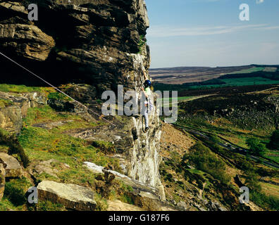 Man climbing Peapod a severe challenging climb on Curbar Edge Peak District Derbyshire England UK  roped to steep - Stock Photo
