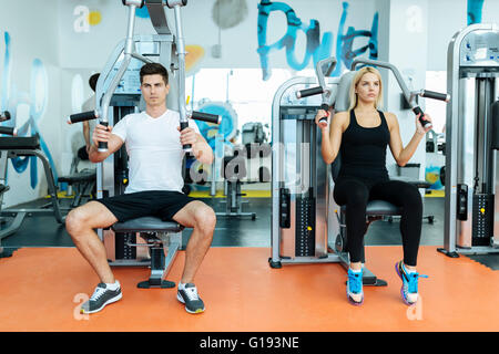People exercising in gym on various machines - Stock Photo