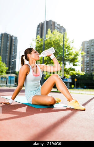 Young beautiful woman drinking water after exercise in a city training court on a sunny day - Stock Photo