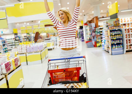 Woman jumping from joy in supermarket from happiness - Stock Photo