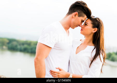 Young beautiful couple rubbing noses as a sign of love and about to kiss each other - Stock Photo