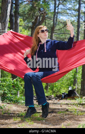 Girl in red hammock, woods - Stockfoto