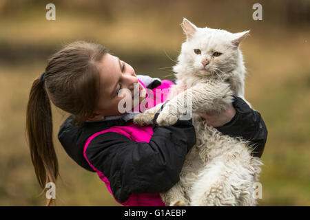 Ten-year girl playing with a stray cat. - Stock Photo