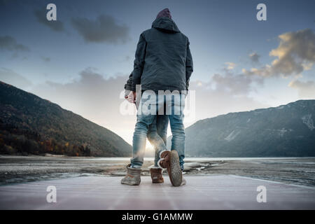 Romantic young loving couple on a pier back view, natural landscape on background - Stock Photo